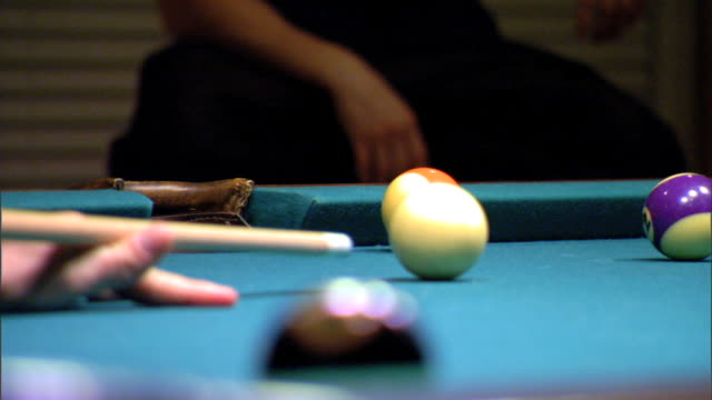 vídeos de stock e filmes b-roll de mcu player taking aim striking white cue ball hitting stripe 12 purple ball sinking into far corner pocket of pool table cue sports cuesports - mesa de bilhar