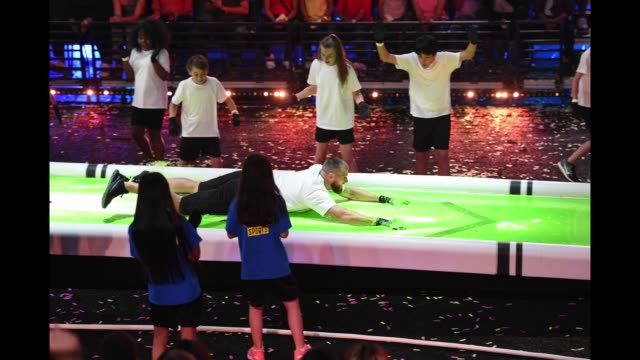 NFL player Travis Kelce is 'slimed' while participating in a challange onstage during the Nickelodeon Kids' Choice Sports 2018 at Barker Hangar on...