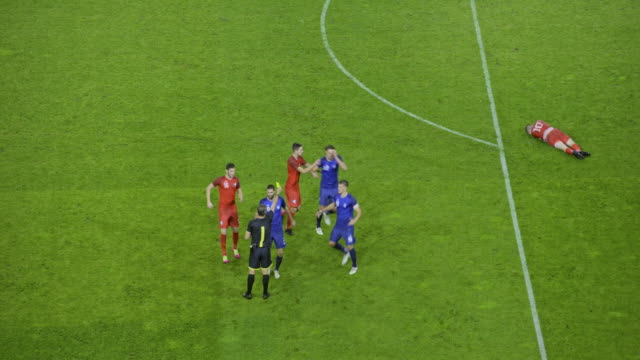 Players arguing after referee shows a yellow card for illegal tackle