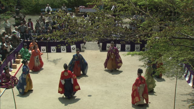 players kick a ball into the air in an open courtyard during a traditional game of kemari. - マリ点の映像素材/bロール