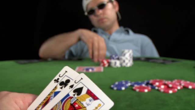 Player's point of view looking at fish-hooks hand as opponent across table rifles stack of chips