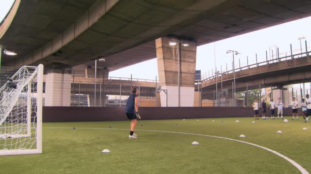 ws pan players shooting at goal, goalie making saves, london, uk - ゴールポスト点の映像素材/bロール