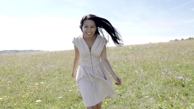 Playful Asian woman running through a meadow.