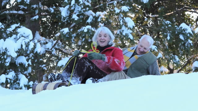 ws ms playful baby boomer couple riding toboggan down hill in snow / richmond, virginia, usa - see other clips from this shoot 1760 stock videos & royalty-free footage
