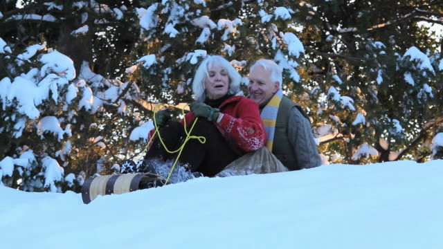WS MS Playful Baby Boomer couple riding toboggan down hill in snow / Richmond, Virginia, USA