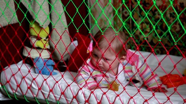 lekfulla baby krypa i spjälsängen - endast en flickbaby bildbanksvideor och videomaterial från bakom kulisserna