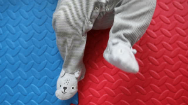 playful baby feet on colorful floor - lying on back stock videos & royalty-free footage