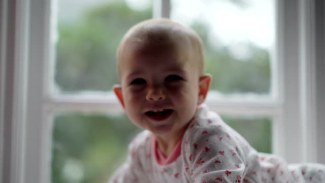 vídeos de stock, filmes e b-roll de playful baby girl lying on alcove window seat - animal de brinquedo