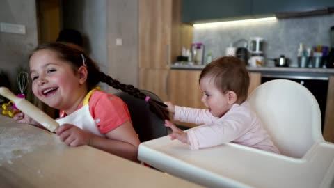 lekfull flicka dra pigtails hennes äldre syster och som får henne att skratta - baka bildbanksvideor och videomaterial från bakom kulisserna