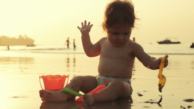 Playful baby in sand on the beach with toys