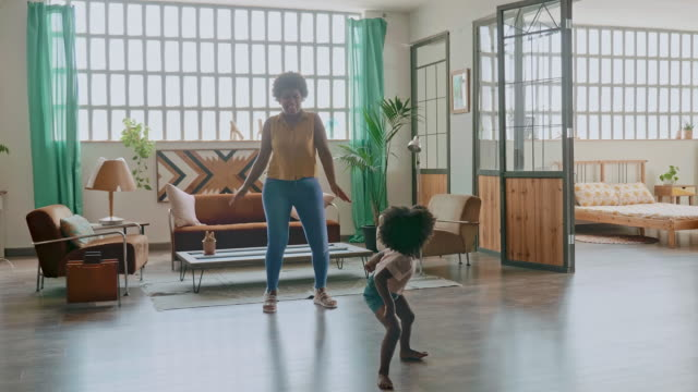 playful bonding between mother and daughter dancing at home - living room stock videos & royalty-free footage