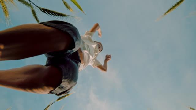 vídeos de stock, filmes e b-roll de menino de ms playful saltando sobre a câmera e trigo abaixo do céu azul - vista de ângulo baixo