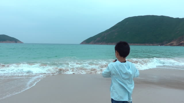 playful boy looking with binoculars at beach - canocchiale video stock e b–roll