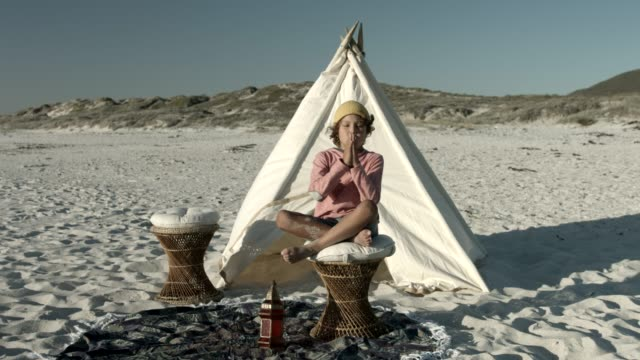 Playful boy mediating against teepee at beach