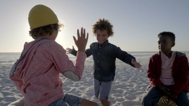 vídeos de stock e filmes b-roll de playful boys enjoying at beach - dar mais cinco