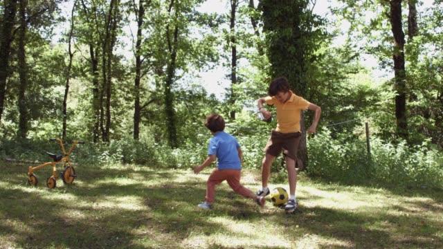 vídeos de stock, filmes e b-roll de lúdicas irmãos jogando futebol na floresta - picnic