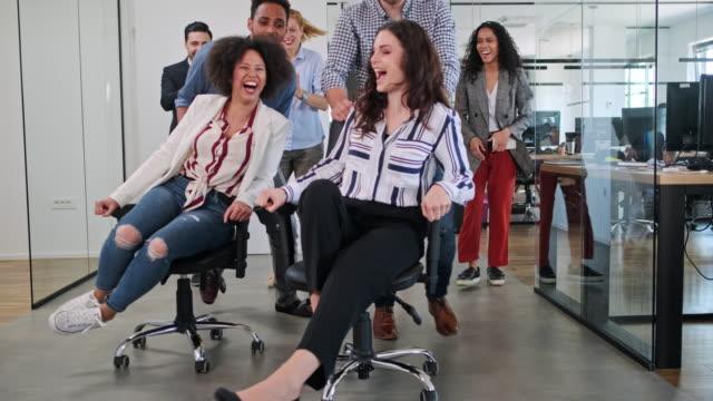 vidéos et rushes de playful business colleagues racing chairs through office (en anglais) - rouler ou dérouler