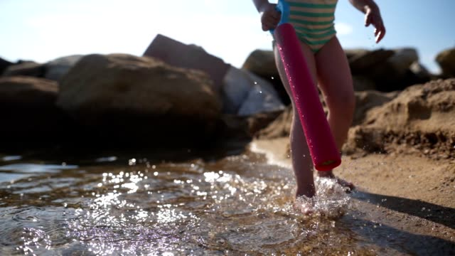 playful child filling a squirt gun from the sea at the beach - sea squirt stock videos & royalty-free footage