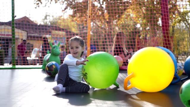 playful child jumping between beach balls on a trampoline - pedana elastica per saltare video stock e b–roll