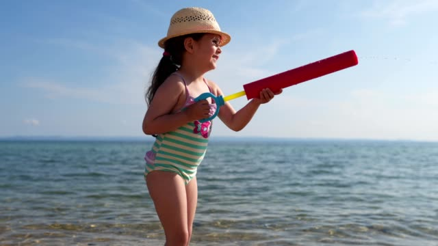 playful child playing with a squirt gun in water at sea - sea squirt stock videos & royalty-free footage
