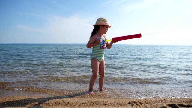 playful child playing with a water gun squirting sea water - squirting girl stock videos and b-roll footage