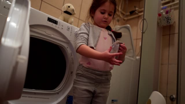playful child removing laundry from a washing machine - laundromat stock videos & royalty-free footage