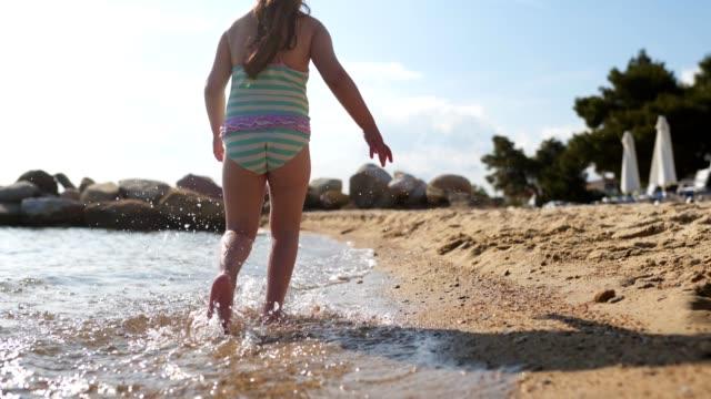 vidéos et rushes de enfant espiègle fonctionnant sur la plage - maillot de bain