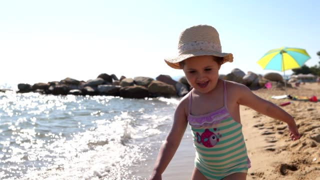 playful child running on the beach - hat stock videos and b-roll footage