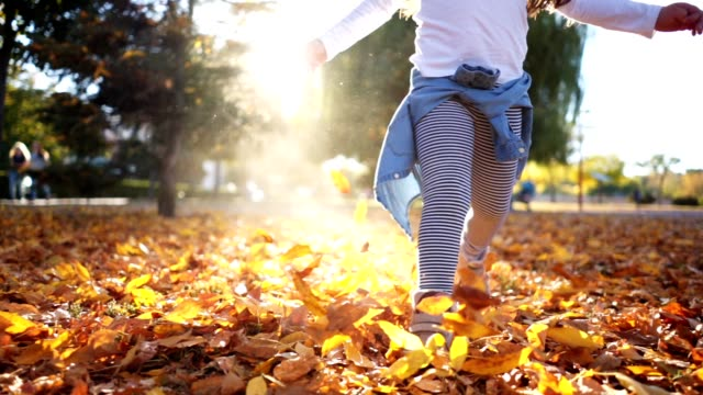 playful child running through a city park through fallen leaves - autumn stock videos & royalty-free footage