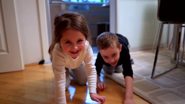 Playful children crawling at home racing each other