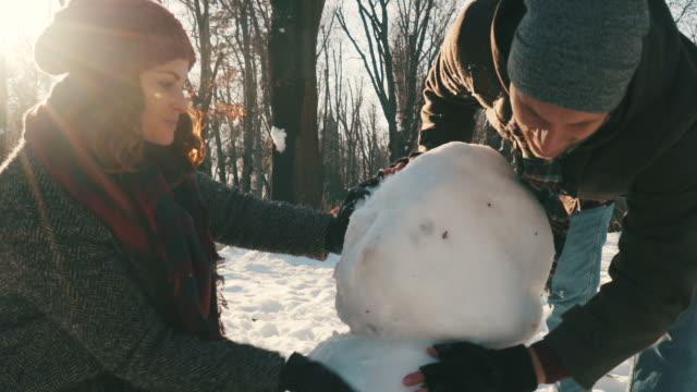 playful couple enjoying winter season. - making a snowman stock videos & royalty-free footage