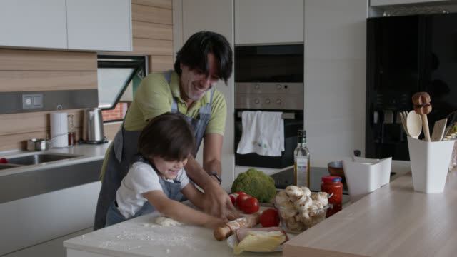 playful daddy and son making pizza and smearing flour on their faces laughing and smiling at home - preparation stock videos & royalty-free footage