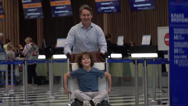 vídeos de stock, filmes e b-roll de paizinho brincalhão que empurra o carro da bagagem quando o filho estiver sentando-se nele no aeroporto excitado e feliz - carrinho meio de transporte