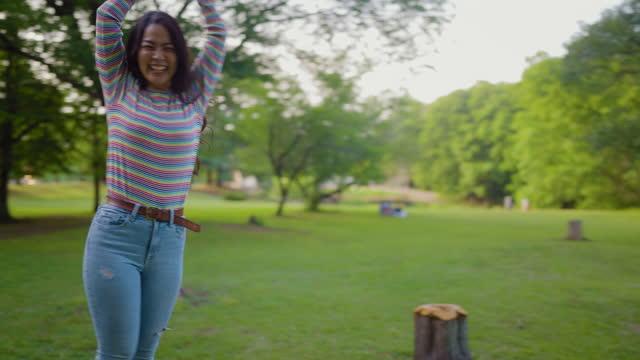 自然の中で遊び心のある有頂天と幸せな若い女性 - beautiful people点の映像素材/bロール