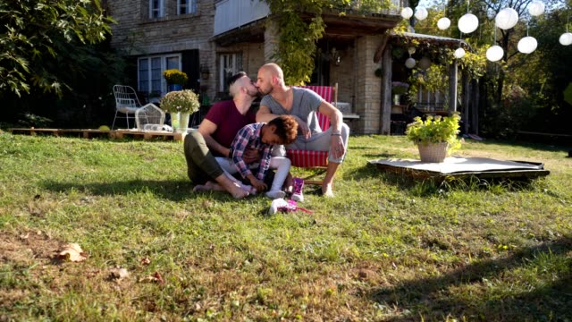 playful family enjoying a sunny day outdoors together - adoption stock videos and b-roll footage