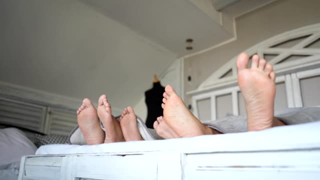 playful family in bed with their feet out - tickling stock videos & royalty-free footage