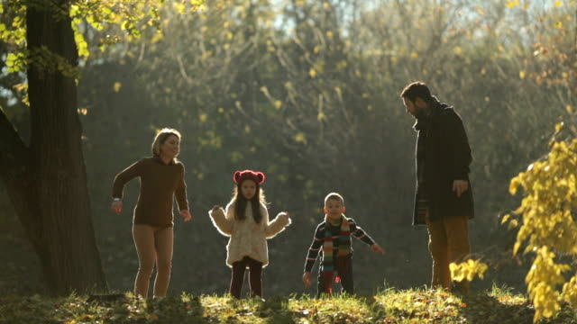 playful family jumping with arms raised and having fun in autumn day. - family with two children stock videos & royalty-free footage
