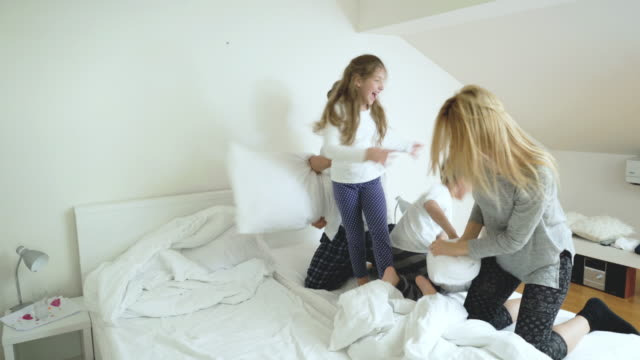 playful family pillow fighting in bedroom and having fun in the morning. - pillow fight stock videos & royalty-free footage