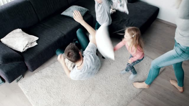 playful family pillow fighting in living room and having fun - pillow fight stock videos & royalty-free footage