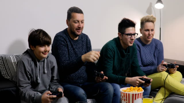 playful family playing video games together in a living room. - gamepad stock videos & royalty-free footage