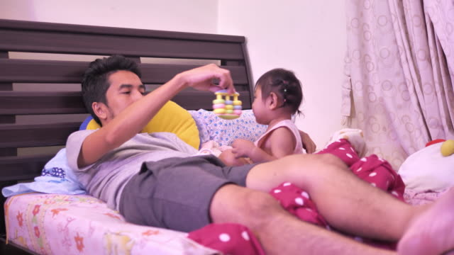playful father and children on bed, relaxed - genderblend video stock e b–roll