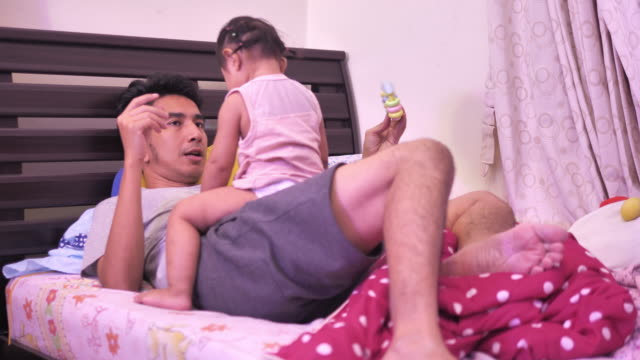 playful father and children on bed, relaxed - genderblend stock videos & royalty-free footage