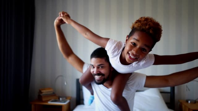 Playful father and daughter having fun in bed