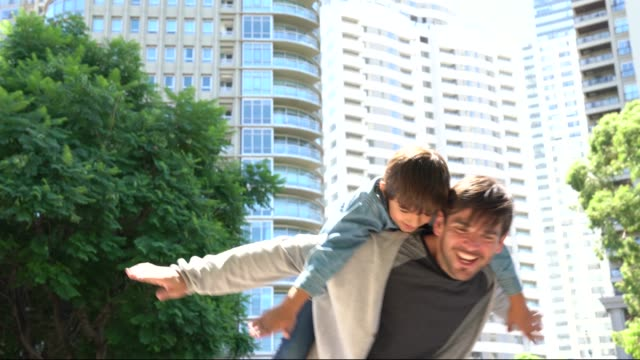 vídeos y material grabado en eventos de stock de padre juguetón llevando a su hijo en la espalda jugando como un avión sonriendo - father day