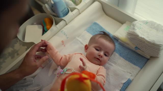 vidéos et rushes de père espiègle jouant avec son bébé - corvée domestique
