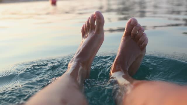 vídeos de stock, filmes e b-roll de pés brincalhão na água de mar. mulher nova que aprecia suas férias de verão - de pé para cima