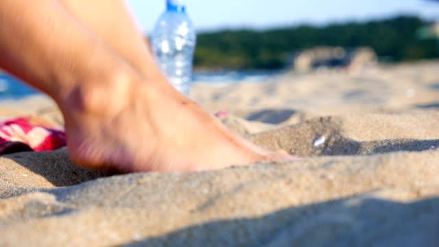Speelse vrouwelijke voeten in het zand van het strand