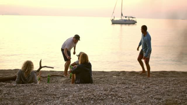 Playful friends hanging out, drinking beer and skipping stones on beach, slow motion