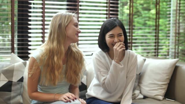 spielerische freunde schauen fern auf dem sofa des wohnzimmers - girlfriend stock-videos und b-roll-filmmaterial