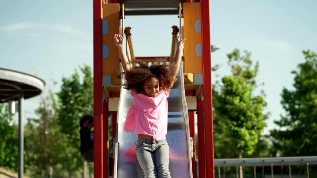 playful girl at a playground - sliding stock videos & royalty-free footage